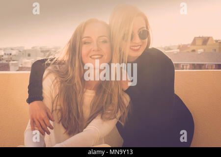 smile and fun for a blonde girls couple outdoor on the terrace roodtop. sunlight in backlight bright image with friendship concept. beautiful models h - Stock Photo