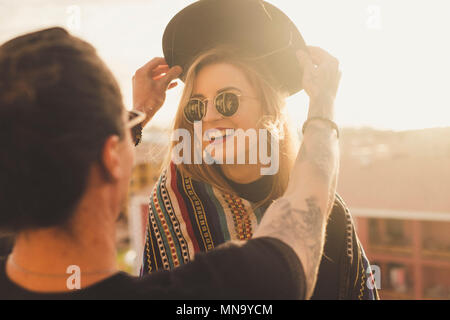 outdoor activity for couple of man and blonde young beautiful woman having fun together. he puts a hat on her head and she smile. sunlight and rooftop - Stock Photo