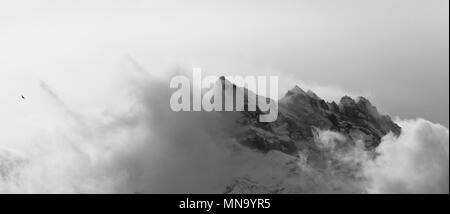atmospheric alpine scenery with clouds moving along a mountain peak - Stock Photo