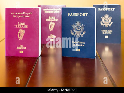 Irish (European Union) and United States of America Passports standing next to each other, and reflected on a wooden table. - Stock Photo