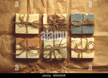 Organic handmade soap on crumpled packing paper. - Stock Photo