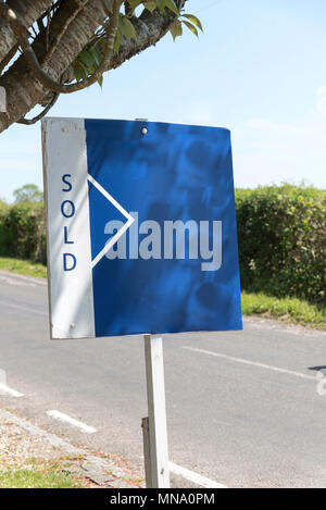 Sold sign outside a property which has been sold - Stock Photo