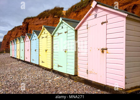 a row of ten beach huts in different colours on the beach at Budleigh Salterton, Devon - Stock Photo