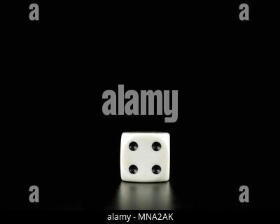Game die isolated against black background, face with number four - Stock Photo