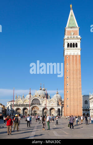 Piazza San Marco, Basilica San Marco and the Campanile at sunset, Venice, Veneto, Italy. St Marks Square, St Marks Cathedral. Scattered tourists in fo - Stock Photo