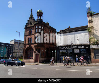 GLASGOW, SCOTLAND - MAY 13th 2018: Cyclists and a car pass the Old College Bar and the Civic Room on High street, Glasgow. - Stock Photo