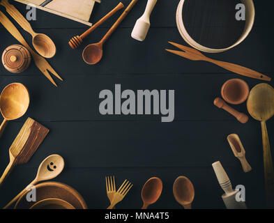 wooden round plates, sieve and rolling pin and other kitchen items on a black table, top view, empty space in the middle - Stock Photo