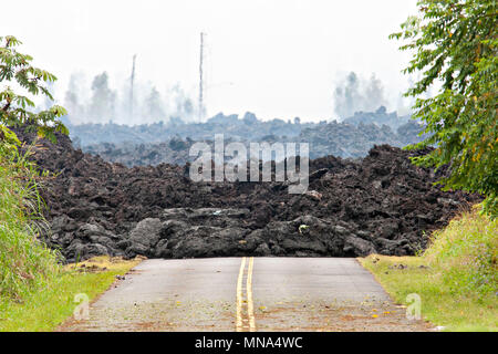 A lava roadblock covers a residential road caused by the Kilauea volcano eruption at Leilani Estates May 12, 2018 in Pahoa, Hawaii. The recent eruption continues destroying homes, forcing evacuations and spewing lava and poison gas on the Big Island of Hawaii. - Stock Photo