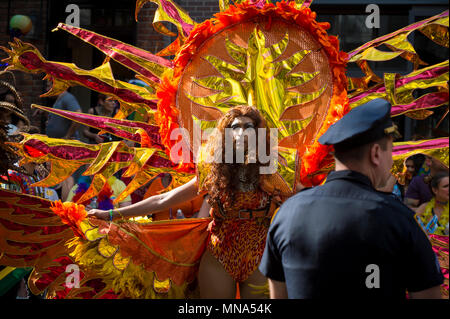 NEW YORK CITY - JUNE 25, 2017: Participant wears orange and gold carnival costume in the annual Pride Parade as it passes through Greenwich Village. - Stock Photo