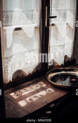 Strong sunlight coming in through a lace curtain - Stock Photo