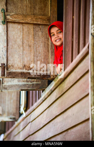 Krabi, Thailand - May 2, 2015: Cute muslim girl wearing red hijap moving out of wooden windows smiling to visitors in rural of Krabi, Thailand - Stock Photo