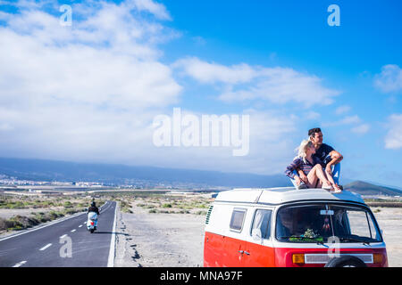 beautiful man and girl couple on the roof of the van for freedom and hippy travel concept. vacation time parked near a long straight road under a blue - Stock Photo