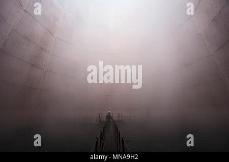 Man standing on walkway in foggy weather - Stock Photo