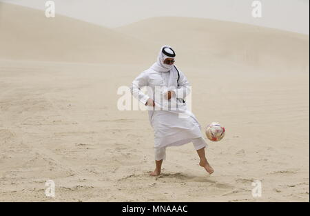 Doha, Qatar. 13th May, 2018. DOHA, QATAR - MAY 13, 2018: A local resident kicks the ball; Qatar is to host the FIFA World Cup in late 2022. Mikhail Aleksandrov/TASS Credit: ITAR-TASS News Agency/Alamy Live News - Stock Photo