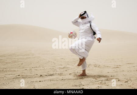 Doha, Qatar. 13th May, 2018. DOHA, QATAR - MAY 12, 2018: A local resident kicks the ball; Qatar is to host the FIFA World Cup in late 2022. Mikhail Aleksandrov/TASS Credit: ITAR-TASS News Agency/Alamy Live News - Stock Photo