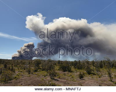 P?hoa, United States. 15th May, 2018. An ash plume rises from the Kilauea volcano on Hawaii's Big Island on May 15, 2018 as seen from Volcano, Hawaii. The Hawaiian Volcano Observatory reports rock falls and gas explosions within Halemaumau Crater have caused an ash plume which is carrying ash downstream across the Kau District. Toxic gas emanating from steaming gashes on the flank of Hawaii's erupting Kilauea volcano added to the danger facing residents, whose escape routes are threatened with closure because of lava flows, officials said. (c) copyright Credit: CrowdSpark/Alamy Live News - Stock Photo