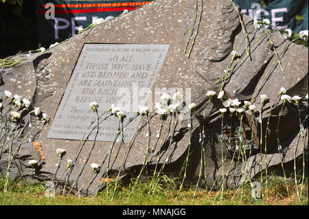 London, UK. 15th May 2018. White carnations laid onto the Conscientious Objectors Commemorative Stone after a ceremony of remembrance held in Tavistock Square, London, UK to mark Conscientious Objectors Day.  79 white carnations were laid at the stone to commemorate various people who have historically refused to kill. Credit: Michael Preston/Alamy Live News - Stock Photo