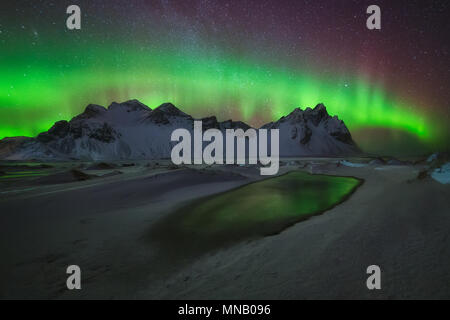 Aurora Borealis green reflection over the water at Stokksnes - Stock Photo