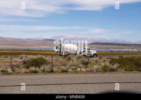 A concrete truck on highway 395 near Crowley Lake in the Eastern Sierra Nevada with the white mountains in the background . California USA - Stock Photo