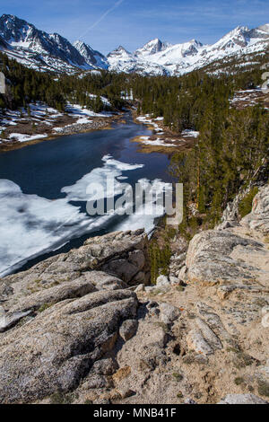 Ice thawing on Mack lake part of the little lake valley trail in the Eastern Sierra Nevada snowcapped  mountains of California USA - Stock Photo