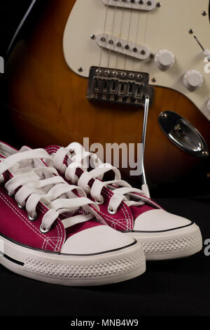 Retro Red sneakers and blurred guitar in background. Close up, selective focus. Rock and Roll fashion concept - Stock Photo