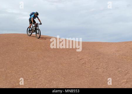 Mountain biker riding downhill the famous Slickrock trail, Moab, USA - Stock Photo