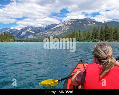 Woman kayaking with red inflatable kayak on Edith Lake, Jasper, Rocky Mountains, Canada - Stock Photo