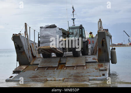 KWAJALEIN, Marshall Islands (March 08, 2018) Equipment Operator 3rd Class Brady Northlee, assigned to Naval Mobile Construction Battalion (NMCB) 11, Construction Civic Action Detail Marshall Islands utilizes an 11K Skytrak to unload project material from a Landing Craft Mechanized (LCM). NMCB-11 is forward deployed to execute construction, humanitarian and foreign assistance, and theater security cooperation in the 7th Fleet area of operations. (U.S. Navy - Stock Photo