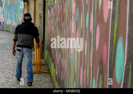 A man, seen from the back, walks in a street of Lisbon, Portugal - Stock Photo