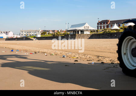 Sandy beach at Whitmore Bay, Barry Island with litter about to be cleaned by tractor the front wheel and shadow of which are in shot. - Stock Photo