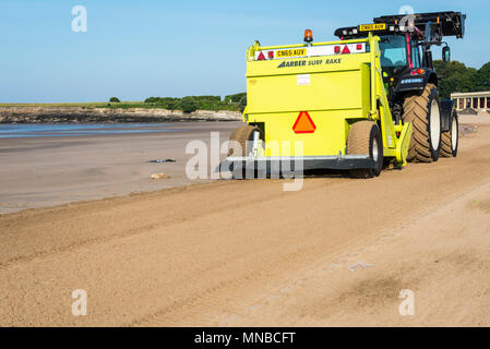 Whitmore Bay beach at Barry Island, Wales, early on a bright sunny summer morning being cleaned of litter by a red Tractor pulling a Barber Surf Rake. - Stock Photo