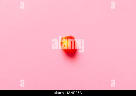 Lonely Apricot  isolated over a fuscia background viewed from above, flatlay style - Stock Photo