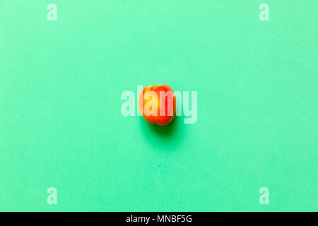 Lonely Apricot  isolated over a green background viewed from above, flatlay style - Stock Photo