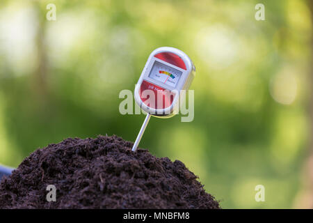 Testing soil using a pH tester to check the acidity of garden compost. - Stock Photo