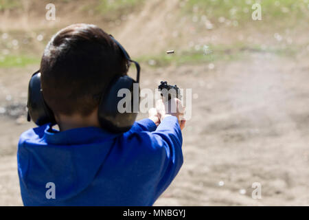 A boy safely practices shooting a pistol at a range in north Idaho. - Stock Photo