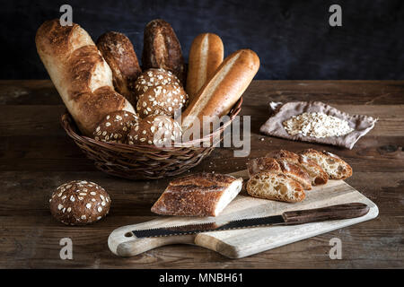 An assortment of bread in a basket and a baguette on the cutting board. - Stock Photo