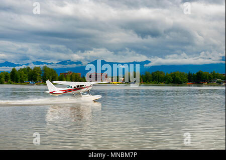 A seaplane taxies to the end of Lake Hood in Anchorage, Alaska, where it will then take off using the length of the lake. - Stock Photo