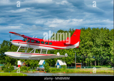 A red and white seaplane takes off on Lake Hood in Anchorage Alaska - Stock Photo