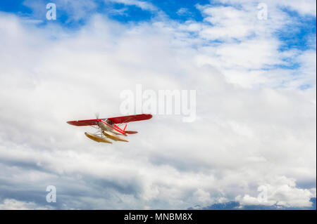 Seaplane files high in the clouds after taking off from Lake Hood in Anchorage, Alaska - Stock Photo