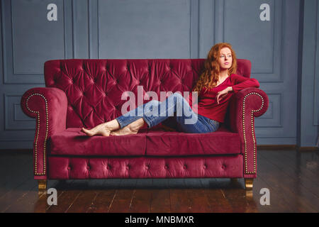 Young rich woman lying on red couch