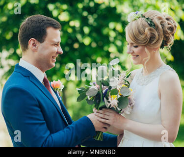 Happy smiling stylish bride and groom  in the summer green park with bouquet of flowers, dancing and having fun on the their wedding day - Stock Photo