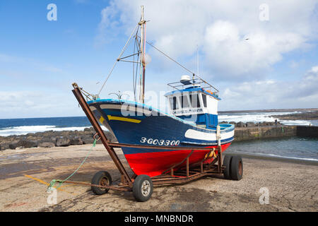 LANZAROTE, CANARY ISLANDS, SPAIN: Colourful fishing boat on a trailer, parked on land in the harbour of La Santa. - Stock Photo