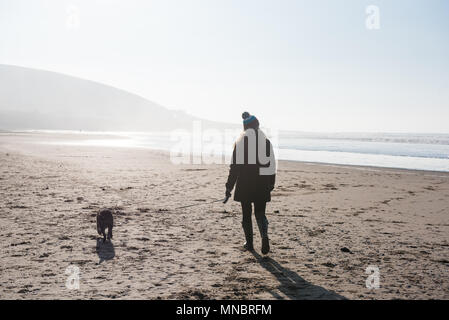 A woman walking her dog on Croyde beach Devon - Stock Photo