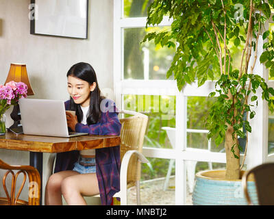 beautiful young asian woman in coffee shop reading blogs using laptop computer. - Stock Photo