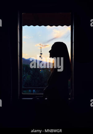 Silhouette of beautiful woman near the window at hotel with sunrise sky in Kyrgyzstan - Stock Photo