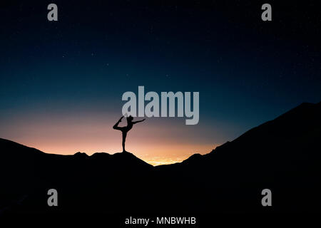 Fit Man in silhouette doing yoga natarajasana pose at night city and starry sky background - Stock Photo