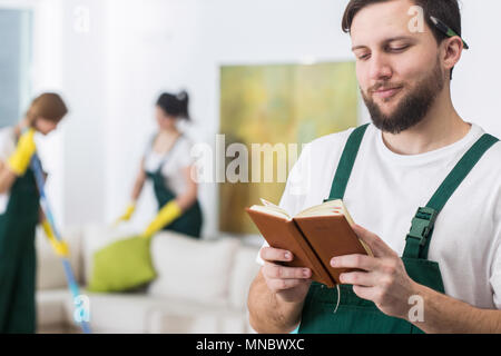 Handsome male cleaner checking calendar with next places to work - Stock Photo