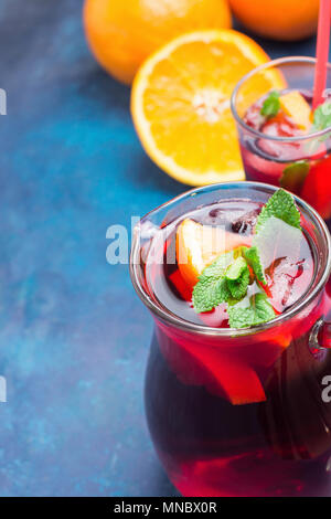 Refreshing Non-Alcoholic Spanish Sangria from Variety of Fruits Orange Citrus Pomegranate Grapes Berries and Fresh Mint in Pitcher and Tall Glass on B - Stock Photo