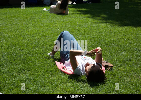 People enjoying the sunshine in Leicester Square London - Stock Photo