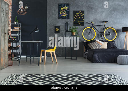 Hipster bedroom with bed, desk, chair and brick wall - Stock Photo